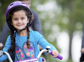 Little Girl (Elementary Age) riding her bicycle outside in the park, wearing a helmet, with her parents following in the background,